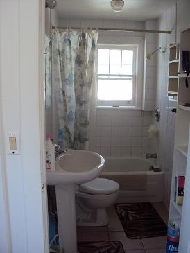 picture of student residence bathroom with toilet, pedestal sink, tub and shower