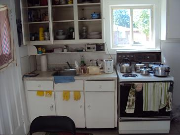 picture of student residence kitchen showing dishes, pots stove and rear window