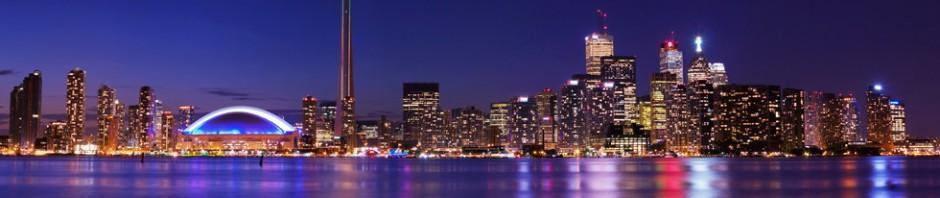 travel picture of  downtown Canadian city at night with lights reflecting across the lake